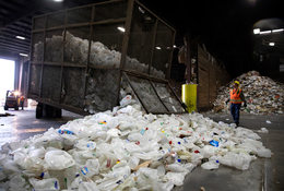 Empty milk containers cover the sorting floor or a materials recovery facility