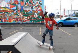 a little boy on a skateboard with a mural as a backdrop