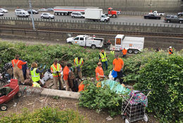 a work crew cleans up a dump site along the highway