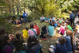 Ed Edmo shares traditions Indigenous stories to group sitting on the ground