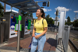 a young woman stands on a MAX train platform holding her fare pass