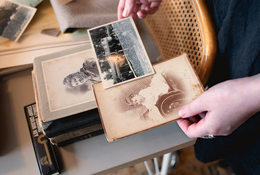 An artist holds turn-of-the-century family photos that she has embellished with paint