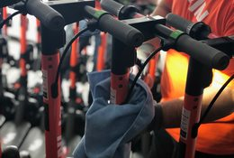 a worker sanitizes a bike in a bikeshare program with a cloth and disinfectant