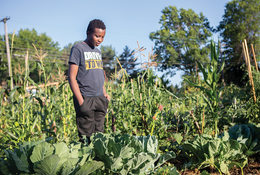 A young black man stands in a garden.