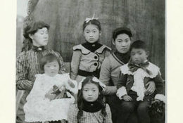 A family of Japanese Americans in formal clothing pose for a photo in front of a huge log. A calico cat hangs out in the foreground.